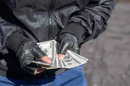 money in the hands of a bandit, a robber who counts the loot