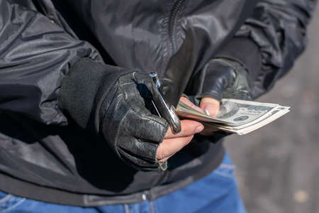 money and a knife in the hands of a bandit, a robber who counts the loot