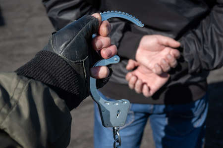 a police officer puts handcuffs on the hands of a bandit 版權商用圖片