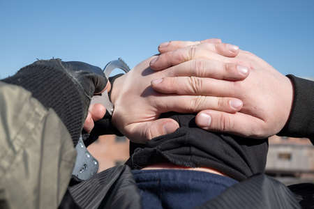 arrest of a criminal, a police officer puts handcuffs on the hands of a bandit