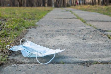 a medical mask lies on a footpath Фото со стока