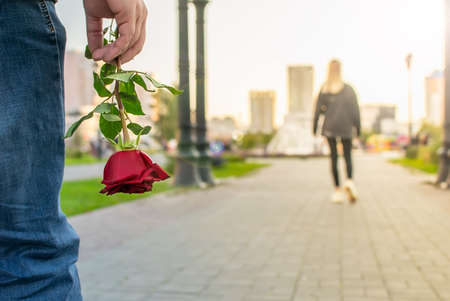 Red rose flower in the hand of a guy