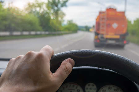 view of the driver hand at the wheel of a car that is driving behind a fuel truck on the road Stock Photo