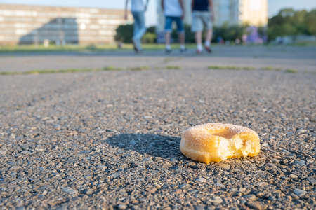 a nibbled donut, a bun, is lying on the track of the stadium Reklamní fotografie