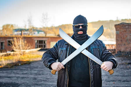 a bandit wearing black glasses and a mask stands with a crossed machete in his hands
