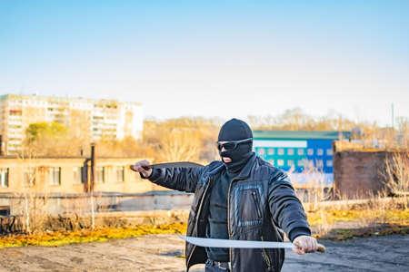 masked bandit trains with a machete in his hands Standard-Bild