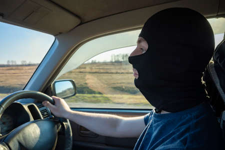 bandit, a black masked driver who drives a car on a country highway Standard-Bild