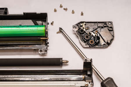 a set of components of the disassembled laser toner cartridge, screwdriver and bolts, lies on a light white surface