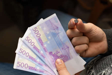 electronic chip, microprocessor, chip and money, banknotes, euros in the hands of a person