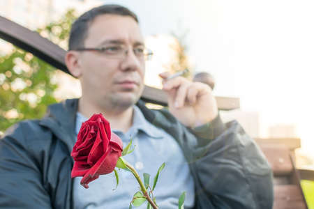 red rosebud in the hand of a thoughtful guy with glasses Standard-Bild