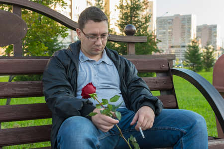a sad, brooding, upset guy with a smoking cigarette and a red rose in his hand sits on a bench in a city park