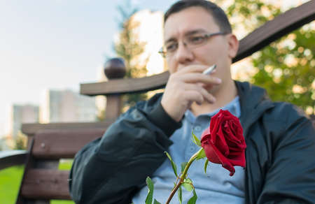 red rosebud in hand and against the background of a thoughtful guy