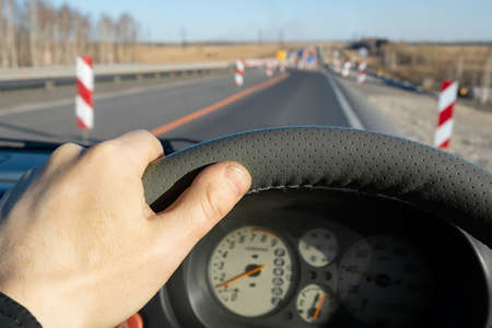 the driver hand on the steering wheel of the car against the background of the road being repaired with fences