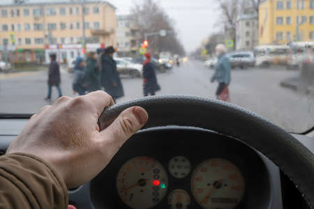 the driver's hand on the steering wheel of the car in front of the pedestrian crossing and passing pedestrians in cloudy rainy weather