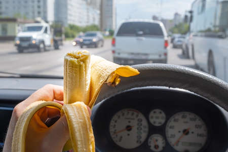 Food, banana in the hand of a driver driving a car that is driving on a city street among city traffic