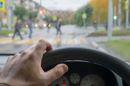 driver's hand on the steering wheel of the car in cloudy weather Standard-Bild