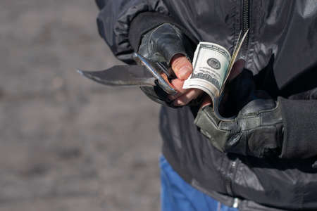 bandit hands hold a knife and count banknotes Standard-Bild