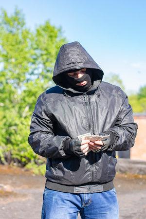 bandit in black mask counts money