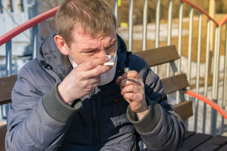 a sick and ill-looking man in a medical anti virus mask tries to light a cigarette on a railway station platform bench