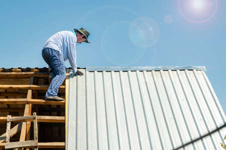 carpenter repairs the roof of the house, attaches metal galvanized sheets in hot weather in the bright sun Standard-Bild