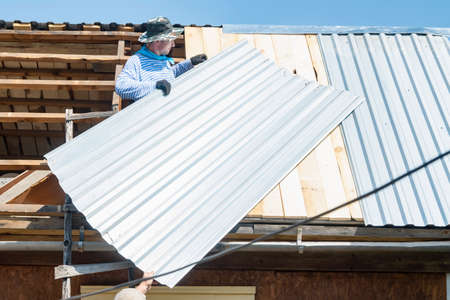 two people, carpenters, builders, lay a galvanized sheet of iron on the roof of the house
