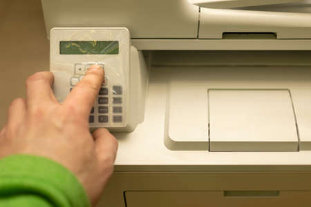 the hand of a person, an office worker, presses the buttons on the control panel of a printer, copier, or multifunction device Standard-Bild