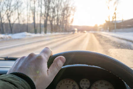 the driver's hand on the steering wheel of the car, which is blinded by the morning sun