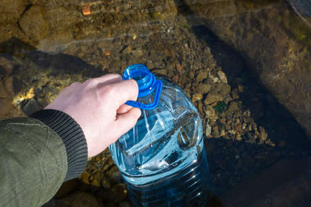 a person's hand holds a plastic bottle with clean spring water Standard-Bild