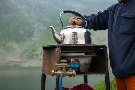 the hand of a boy, a teenager, holds the lid of a metal camping kettle, which stands, boils on the fire of a gas stove