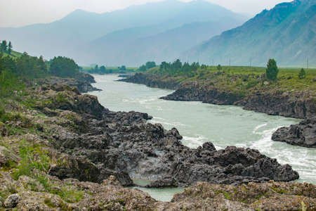 natural landscape of the river with rocky banks among high mountains in fog in cloudy weather