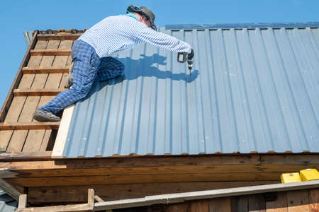 a rural male builder repairs the roof of a house
