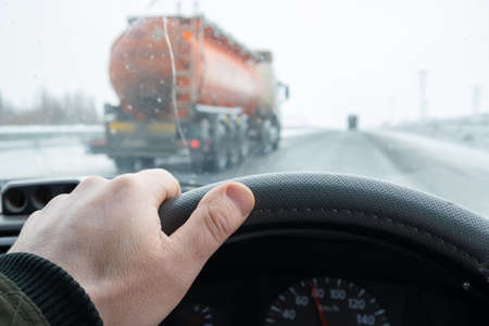 the driver's hand on the steering wheel of the car, which is overtaken on the secondary line by a tanker truck with a large tank of fuel