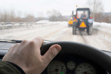 driver hand behind the wheel of a car that drives behind two slow moving tractors