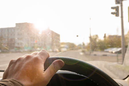 the driver hand on the steering wheel of a car that is blinded by bright sunlight Standard-Bild