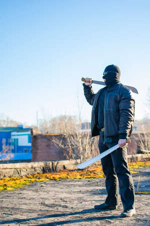 a bandit, a terrorist wearing glasses, a mask and black clothes, ready to attack, holds two machetes