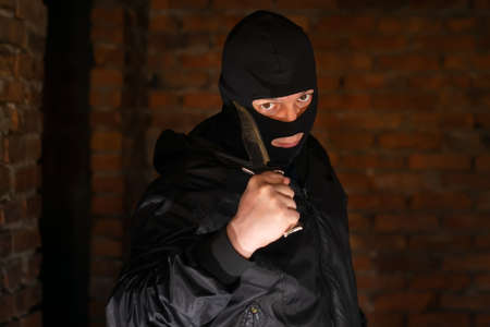 a bandit in a black mask threatening with a knife in a room of an empty building under construction on a dark background at night Standard-Bild