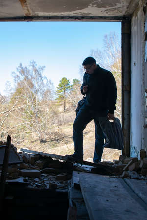 a man with things came to the destroyed house and sadly examines the wreckage of the broken structure