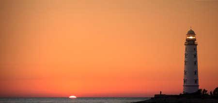 tybee island: Lighthouse searchlight beam near ocean at sunset Stock Photo