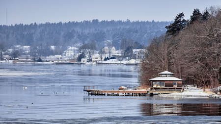 Sweden house in the wintertime. Nature on the shore of the fjord.