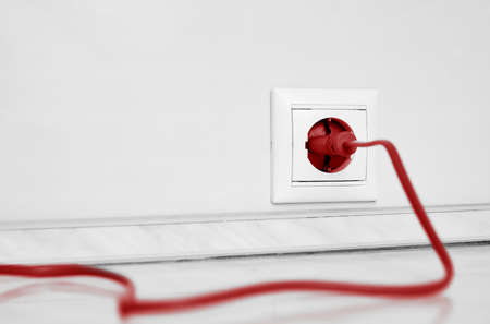 Electric white socket and one plugged in power cord on white wall background.