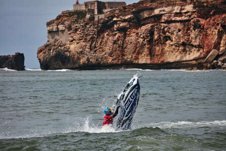 Professional jet ski riders compete at the IFWA World Tour Jet Ski Championship. Contestants perform tricks for judges in the waves. Freeride World Championship IFWA. 27.04.2018, Nazare, Portugal Banque d'images - 139965234
