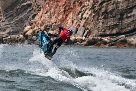 Professional jet ski riders compete at the IFWA World Tour Jet Ski Championship. Contestants perform tricks for judges in the waves. Freeride World Championship IFWA. 27.04.2018, Nazare, Portugal Banque d'images - 139965238