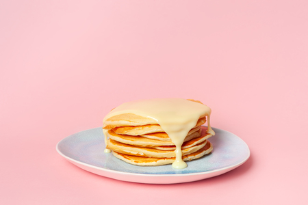 Pancakes with condensed milk or milk sauce on a blue plate. On a pink pastel background. The concept of a delicious Breakfast. Side view. Place for text