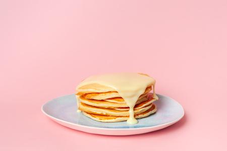 Panqueques con leche condensada o salsa de leche en una placa azul. Sobre un fondo rosa pastel. El concepto de un delicioso desayuno. Vista lateral. Lugar para el texto Foto de archivo