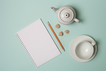 Tea kettle, Cup and saucer, brown sugar, notebook and pencil. On a pastel blue background. The concept of Breakfast. Top view