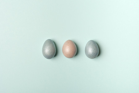 Easter, silver, blue eggs on a blue  background.  The minimum concept of Easter. Easter card with space for text. The view from the top