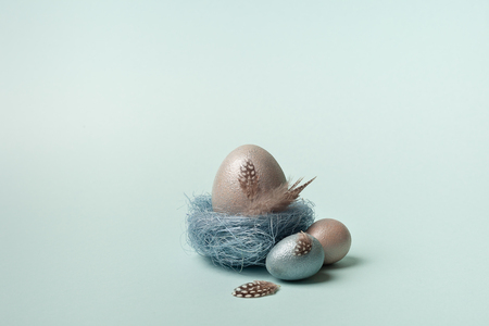 Easter, silver, blue eggs on a blue  background. Decorated with feathers.  In the nest of sisal fibre. The minimum concept of Easter. Easter card with space for text. The view from the top