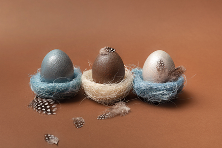 Easter, silver, brown, blue eggs on brown background. Decorated with feathers.  In the nest of sisal fibre. The minimum concept of Easter. Easter card with space for text. Top view