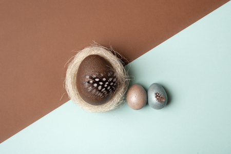 Easter, silver, brown, blue eggs on brown - blue background. Decorated with feathers. In the nest of sisal fibre. The minimum concept of Easter. Easter card with space for text. Top view