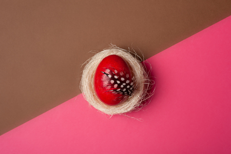 Easter, pink egg on a brown- pink background. Decorated with feathers.  In the nest of sisal fibre. The minimum concept of Easter. Easter card with space for text. Top view Stock fotó - 122056239